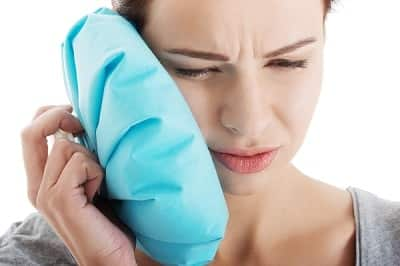 A woman with TMJ pain, treats it with hot pack